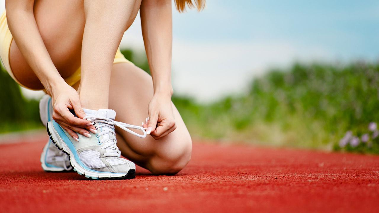 Sports shoes in test - Expensive or cheap - Woman ties sports shoes