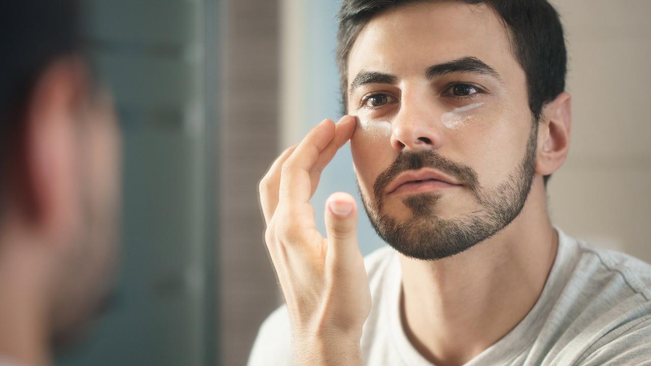 Which care cream does the modern man need - man applies eye cream