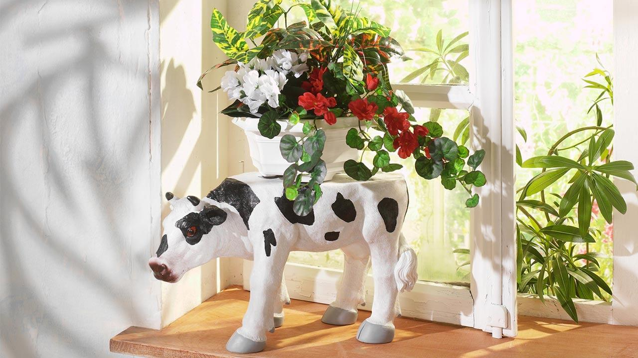 Nice summer decoration on the windowsill / a cow with flowers