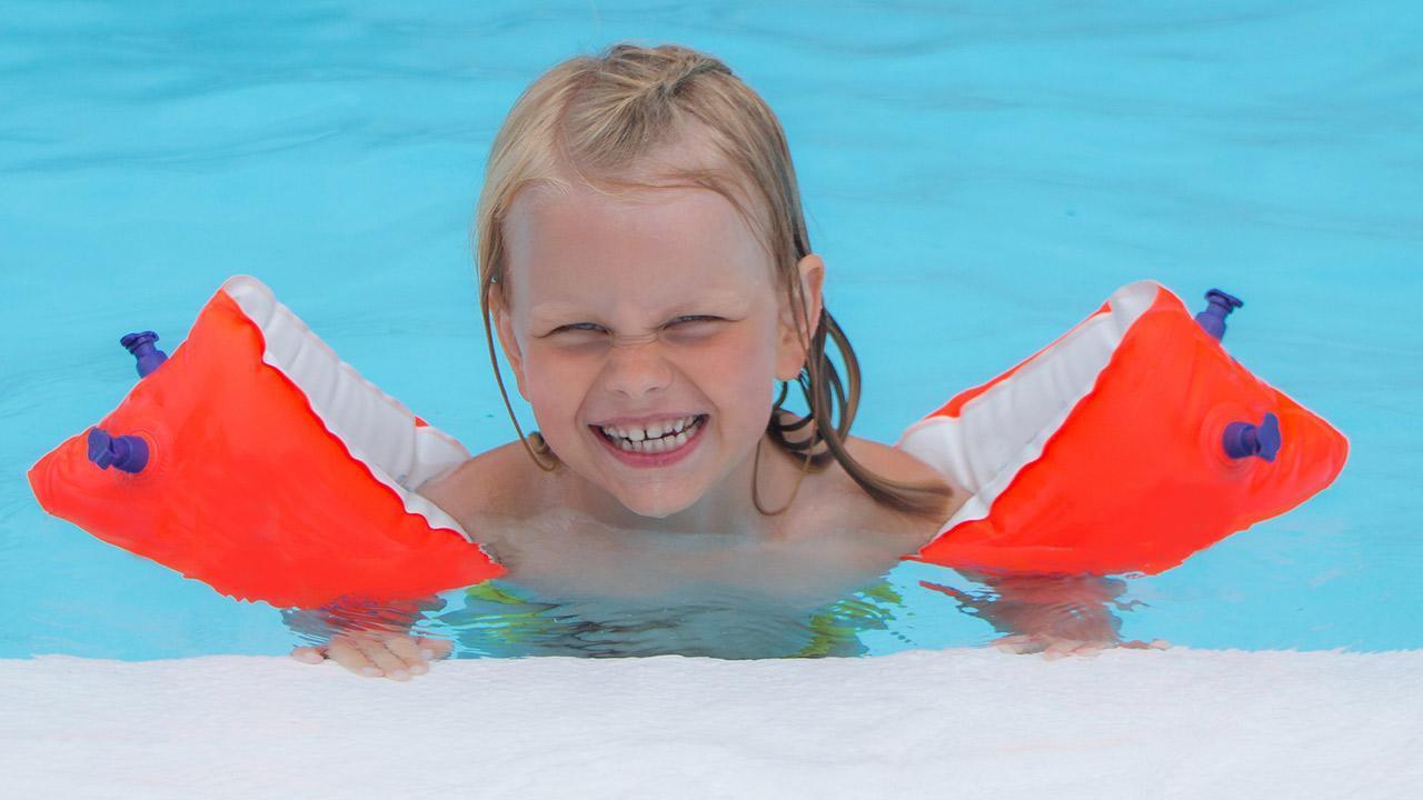 The best buoyancy aids for children / little girl wearing water wings