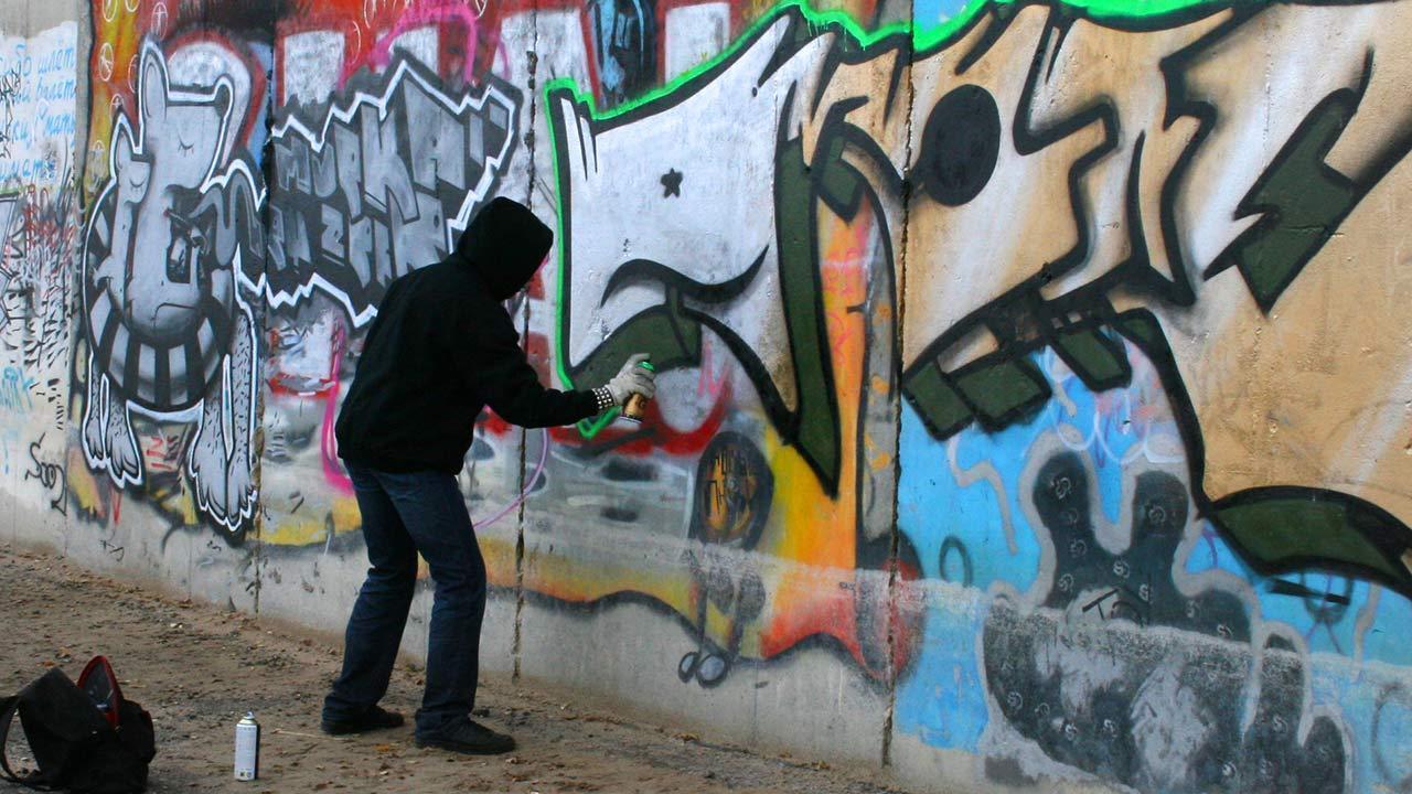 Graffiti - introduction to hobby painting / a man sprays graffiti