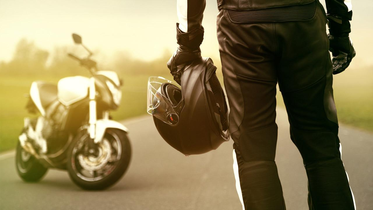 Motorcycle helmet - what do I have to pay attention to? / Man with helmet next to a motorcycle