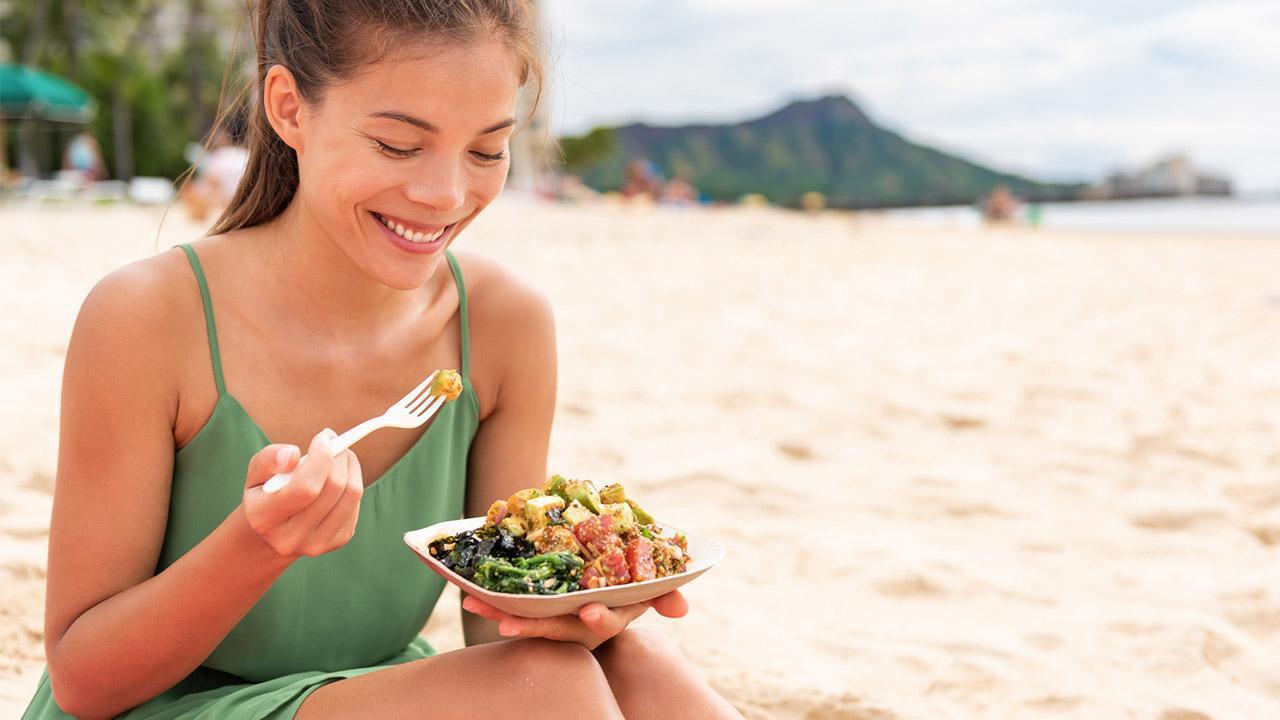 Poke - fish salad from Hawaii / a woman eats a poke