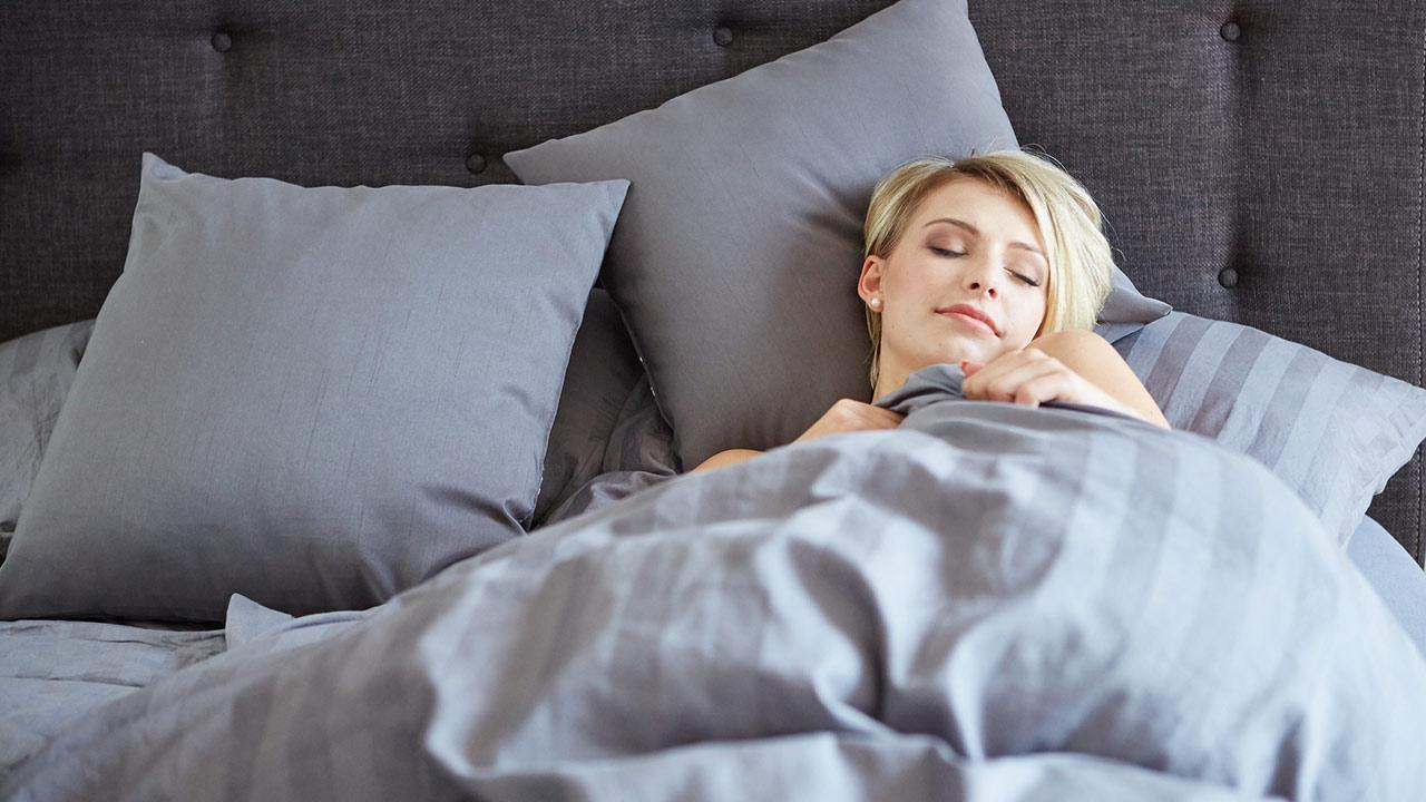 Warm bed linen in winter-Which materials are the best / Woman lying in bed